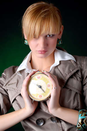 beautiful woman with alarm clock on a black background photo