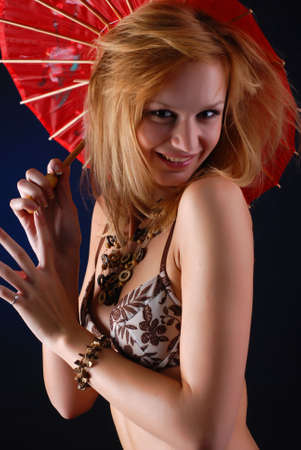 portrait of a beautiful blond woman in lingerie with red parasol photo