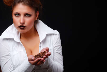 portrait of beautiful young woman with coffee beans in her hands photo