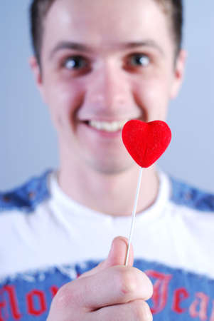 Man takes a red heart at blue background Stock Photo - 4279161