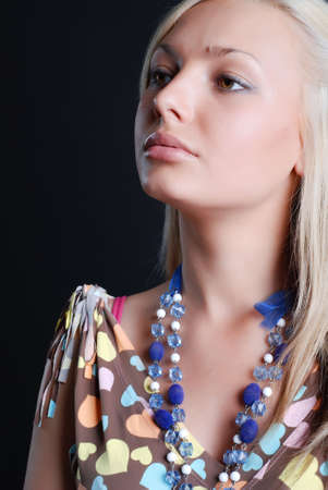 The beautiful girl in a sundress with a beads on a neck photo