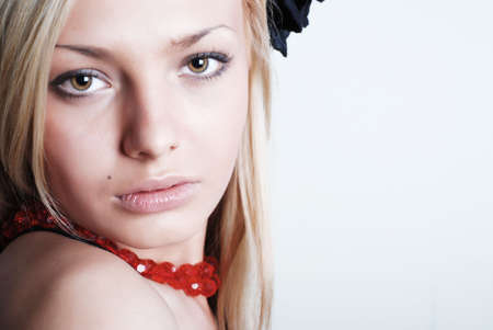 The beautiful blonde with red roses on a neck and a black rose in hair photo