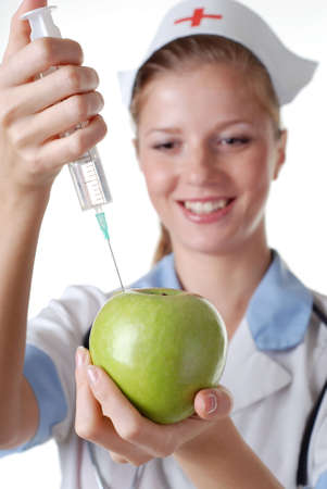 nurse with syringe make injection in green apple photo