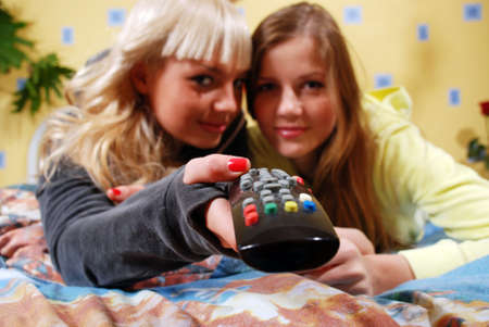 two beautiful women watching television at the bedroom Stock Photo - 4407269