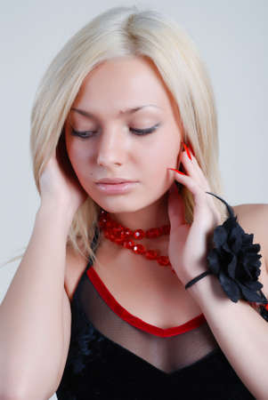 The beautiful blonde with red roses on a neck and a black rose on hand photo