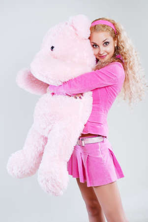 The girl dressed in pink with a teddy-bear in hands photo