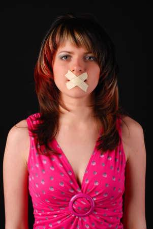 kokhalzen: jonge vrouw met kruis van gips op haar mond
