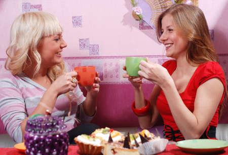 two beautiful women drinking tea at the kitchen photo