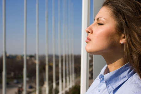 beautiful woman with closed eyes standing near the window photo