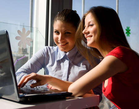 two beautiful women sitting in cafe with laptop photo