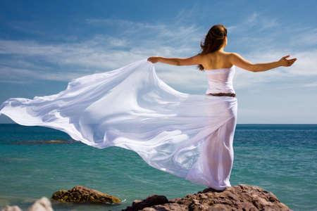 mermaid: Beautiful woman in white dress at the sea beach  Stock Photo