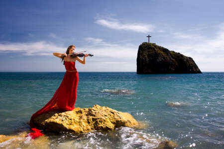 Beautiful woman with violin at the sea beach
