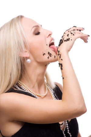 Beauty woman eat black caviar from her hands photo
