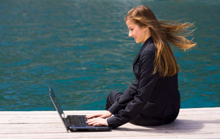 woman in black business suit sitting with laptop near the sea photo