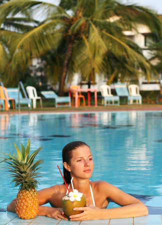 young beautiful woman in pool with coconut and pineapple photo