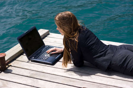 mobility: woman in black business suit lying with laptop near the sea Stock Photo
