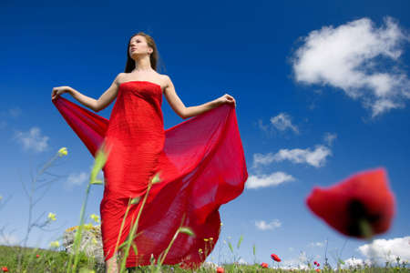 young beautiful woman in red dress standing on the field photo