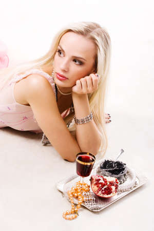 young luxurious blond woman in pink dress with silver tray photo