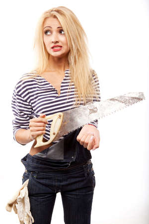 young blond woman in denim with big saw   photo