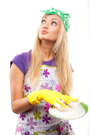 chore: young beautiful housewife in yellow gloves with plate  Stock Photo