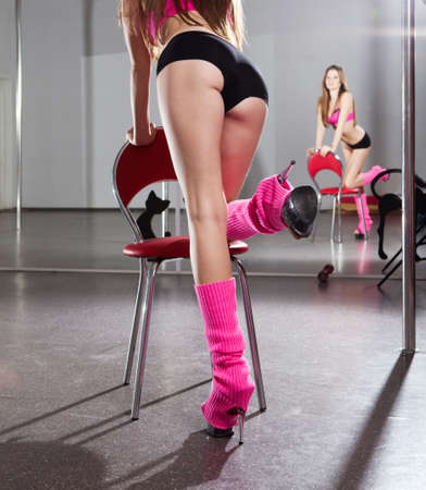 young beautiful woman in pink sportswear on the red chair  photo