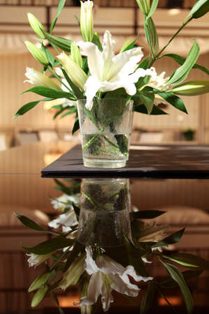 beautiful lily in glass vase on the table photo