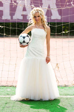 young beautiful bride standing on the gate with ball photo