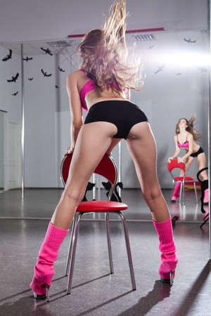 voluptuosa: hermosa joven en ropa deportiva Rosa en la silla roja