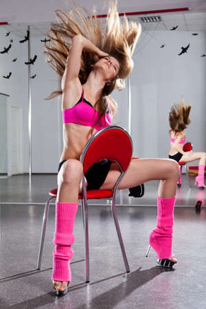 young beautiful woman in pink sportswear on the red chair  Stock Photo