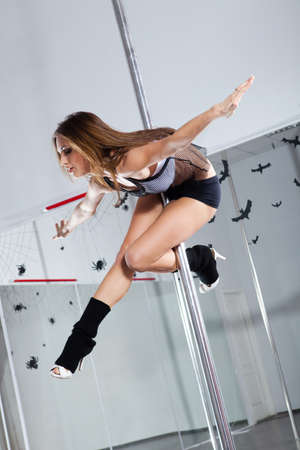 female stripper: Young athletic woman dancing around the pole