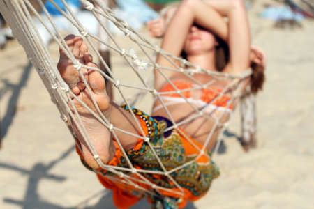Woman taking sunbath in hammock on the beach