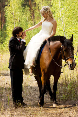 Bride and groom in forest with horses
