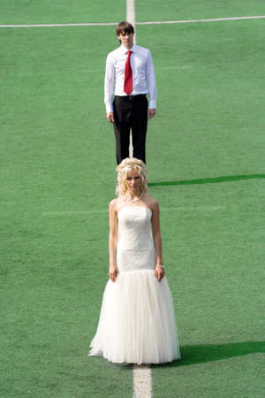 Bride and groom on football stadium photo