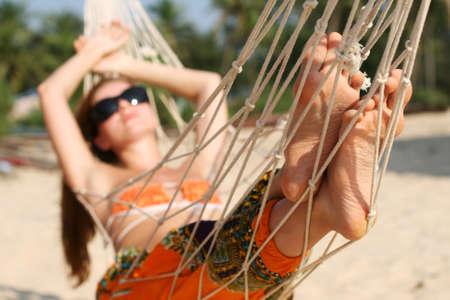sunbath: Vrouw nemen zonnen in een hangmat op het strand Stockfoto