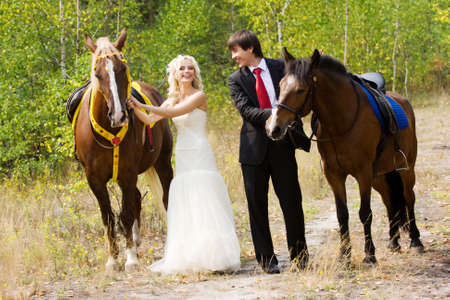 Bride and groom in forest with horses photo