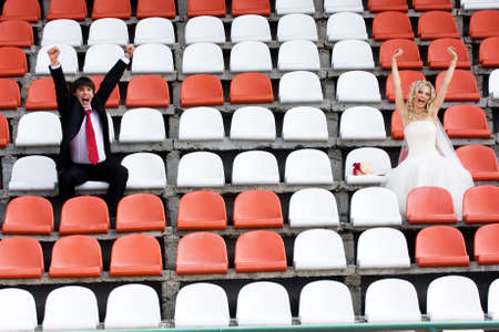 Bride and groom on the sport stadium seats photo