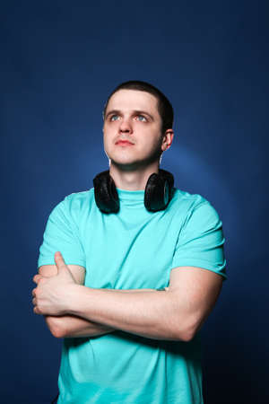 Man with headphones listening music at blue background photo