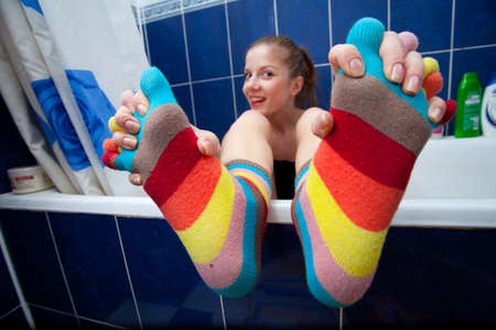 Crazy girl in bathroom weared in color striped socks