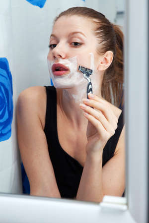 Funny girl shaving her face in bathroom Stock Photo - 11011981