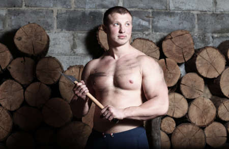 Ņhatchet: Young strong man with hatchet and a lot of woods Stock Photo