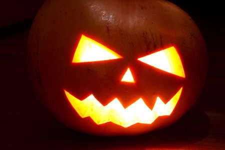 Angry face of helloween pumpkin at black background photo
