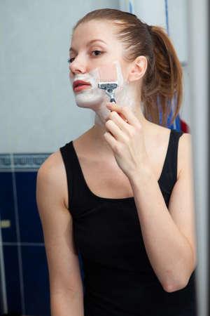 Funny girl shaving her face in bathroom photo