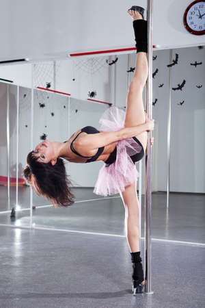 Young athletic woman dancing around the pole photo