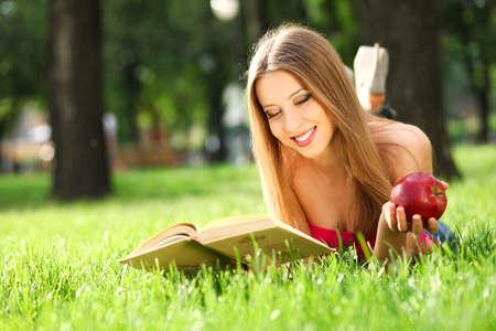 mujer leyendo libro: Mujer leyendo un libro en el parque en la hierba