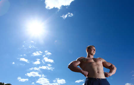 Strong man athlete outdoor with blue sky photo