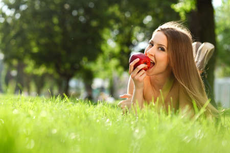 Woman reading book in the park on the grass Stock Photo - 12747100
