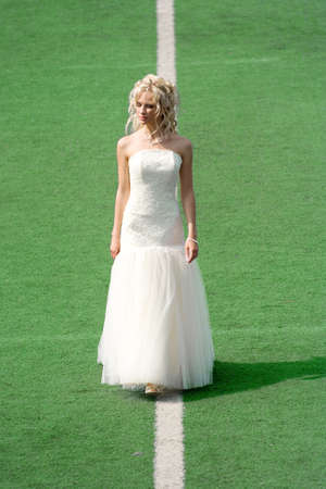 Bride on the football field with green grass photo