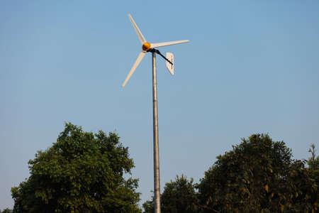 Windmills against the blue sky and green trees photo