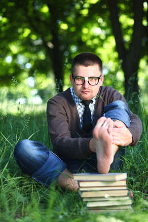 A man in glasses sitting on green grass with books Stock Photo - 13316650