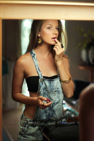Beautiful woman in swimsuit and dungarees standing near the mirror with pink lipstick photo